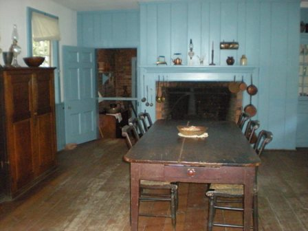 How about the rich milky turquoise on these walls? The lovely color surprised me. Isn't this a stunning kitchen? Homesteaders usually started out with a small log cabin as a first home, as quickly as they could clear the trees to make room. This would've been their second house, after living off the land for sixteen years – a two-story structure with more expensive furniture.